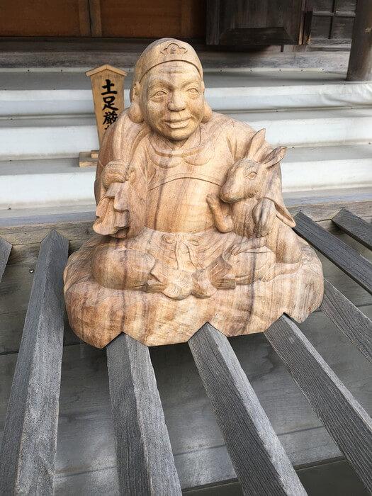 お賽銭入れの木彫り像